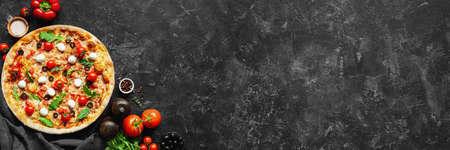 Italiaanse pizza en pizza kokende ingrediënten op zwarte concrete achtergrond. Trostomaten, mozzarella, zwarte olijven, kruiden en specerijen. Kopieer ruimte voor tekst. Banner samenstelling