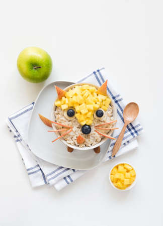 Oatmeal porridge with cute funny face, kids breakfast. Good morning breakfast for kids, food art. White background