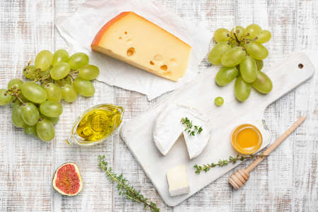 Camembert, yellow cheese, fruits and herbs on white wooden background. Cheese plate, appetizer plate. Top view Фото со стока