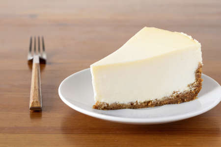 Slice of plain New York Cheesecake on wooden table. Horizontal composition