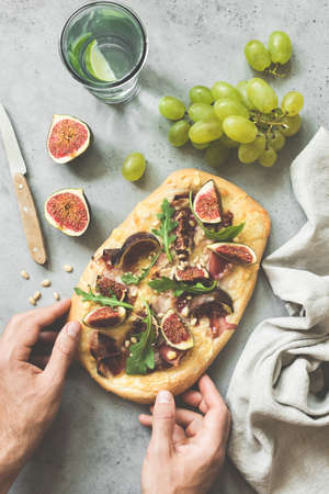 Flatbread or pizza with figs, arugula, prosciutto. Autumn pizza with fruits and ham. Hands holding flatbread pizza over concrete background. Top view, toned image