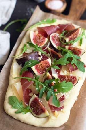 Pizza or flatbread with fig, prosciutto, cheese, arugula on wooden serving board. Selective focus