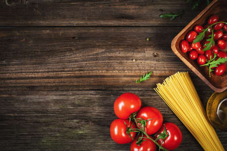 Pasta, tomatoes, olive oil and herbs on wooden background. Italian cuisine food ingredients for cooking. Copy space for text Фото со стока