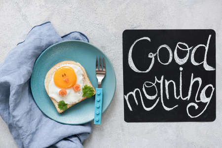 Breakfast food kids. Funny toast with egg and good morning text on a chalkboard. Top view