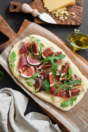 Flatbread pizza with ham, figs, arugula on wooden board. Top view Фото со стока