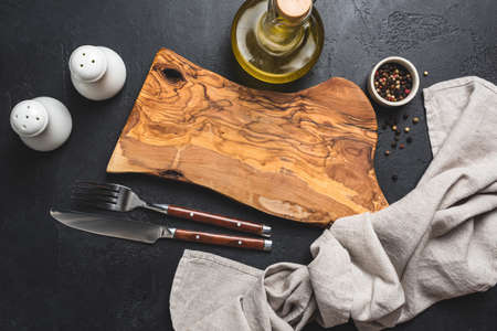 Table setting on black concrete background. Olive wood cutting board, cutlery, salt and pepper, olive oil and kitchen linen textile Фото со стока