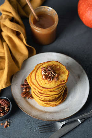 Pumpkin pancakes with caramel sauce and pecan on a plate. Top view, selective focus. Tasty pancakes autumn comfort food