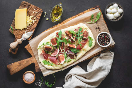 Homemade pizza or flatbread with figs, ham, arugula, cheese on wooden serving board. Table top view Фото со стока