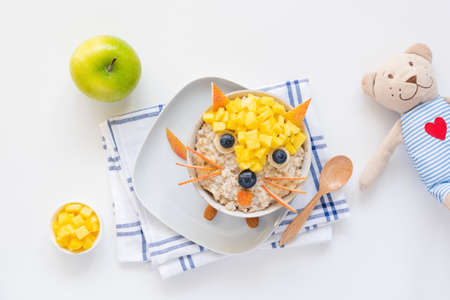 Breakfast for kids, children meal Oatmeal porridge bowl decorated using fruits and berries as cute funny fox and teddy bear on side. Food art
