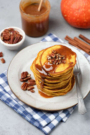 Pumpkin pancakes with caramel sauce, cinnamon and pecan nuts. Vertical, selective focus