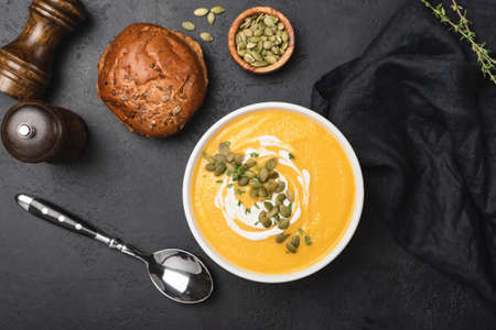 Tasty pumpkin cream soup in bowl over black concrete background. Table top view, selective focus