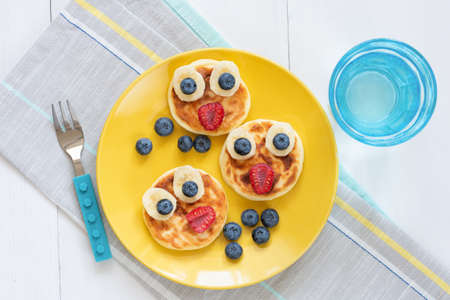 Breakfast pancakes for kids. Funny cute animal shaped pancakes on a yellow plate. Top view. Food art