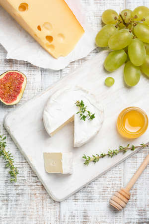 Brie or camembert cheese served with fruits and honey on white cheeseboard. Top view