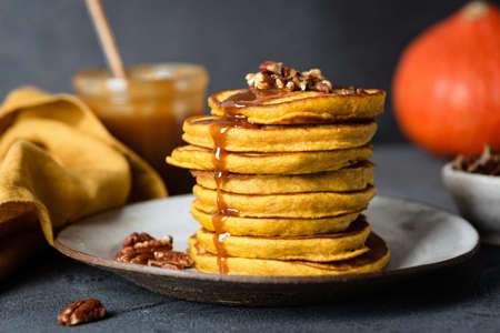 Pumpkin pancakes with caramel sauce and pecan nuts, black concrete background. Closeup view, selective focus