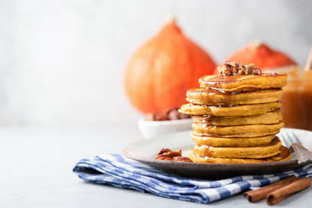 Tasty pumpkin pancakes with nuts and caramel sauce on grey concrete background. Horizonta, copy space for text or recipe, selective focus Фото со стока