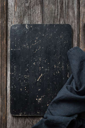 Black cutting board or blackboard on wood. Copy space for text. Menu, recipe or food background