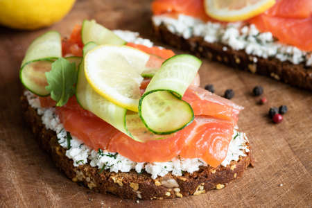 Rye toast with smoked salmon, cucumber and cream cheese on rustic wood background, closeup view Фото со стока