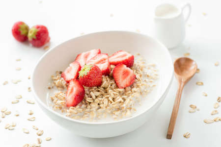 Oats porridge with fresh strawberries and milk. Healthy breakfast oatmeal with fruits on white background Фото со стока