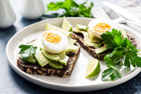 Toast with avocado and boiled egg on a plate, closeup view. Healthy breakfast, healthy eating or snack concept Фото со стока