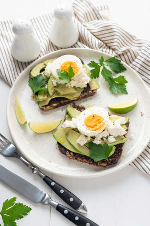 Wholegrain toast with avocado, egg and soft cheese on white plate, healthy breakfast healthy eating concept Фото со стока