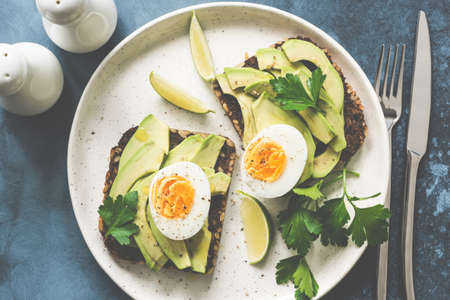 Healthy avocado toasts with boiled egg on a plate. Top view, toned image