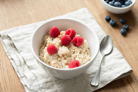 Oatmeal porridge with berry fruits on linen textile. Healthy breakfast food, dieting and healthy eating concept