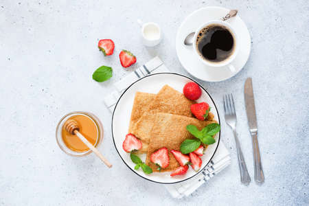 Crepes or blinis with strawberry, coffee cup and honey. Tasty gourmet breakfast, bright blue concrete background. Top view