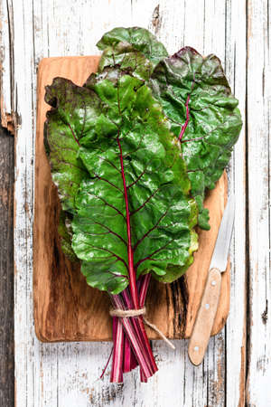 Swiss chard leaf on wooden background. Top view. Green, vegan, vegetarian or clean eating concept
