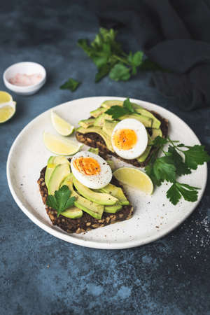 Healthy toast with avocado and egg. Whole grain rye toast on white plate