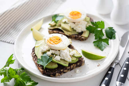Healthy tasty toast with avocado, white cheese and boiled egg on white plate, closeup view, selective focus