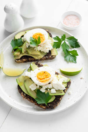 Rye bread toast with avocado, egg, white cheese on a plate. Healthy breakfast, healthy eating concept Фото со стока