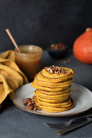Stack of tasty pumpkin pancakes with pecans and salted caramel sauce. Selective focus