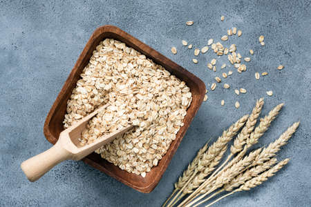 Rolled oats in wooden bowl on concrete background, top view. Concept of healthy eating, agriculture, healthy lifestyle and dieting Фото со стока
