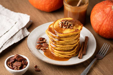 Homemade pumpkin pancakes with cinnamon, caramel and nuts on rustic wooden table Фото со стока
