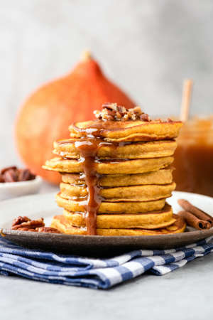 Pumpkin pancakes with caramel sauce and nuts on plate, closeup view, vertical composition