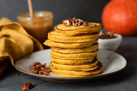 Pumpkin pancakes with pecan nuts and salted caramel sauce on a plate. Healthy tasty autumn comfort food