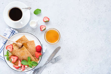 French crepes or blini with strawberries, honey and cup of coffee on table. Top view and copy space for text, recipe or restaurant cafe menu Фото со стока