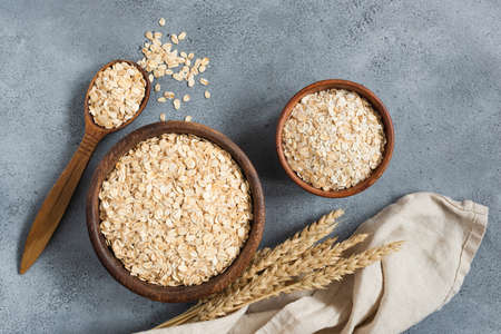 Rolled oats and oat flakes in wooden bowl on concrete background, table top view. Healthy eating, dieting, yoga and fitness concept