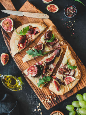 Pizza or flatbread with fig, prosciutto, parmesan cheese, arugula on wooden cutting board, top view