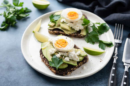 Healthy rye toast with avocado, egg, feta cheese on white plate. Healthy tasty breakfast, lunch or snack 스톡 콘텐츠