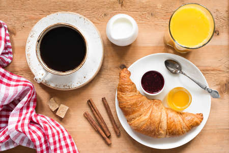 Breakfast table with croissant, coffee, orange juice and jam. Rustic wood table background, top view