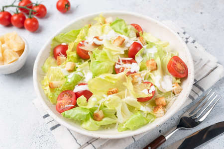 Caesar salad on white plate, closeup view. Served fresh tasty salad