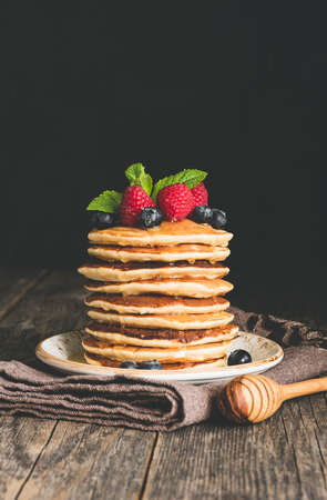 Pancakes with berry fruits, honey and mint leaf on rustic wooden table. Vertical, copy space for text