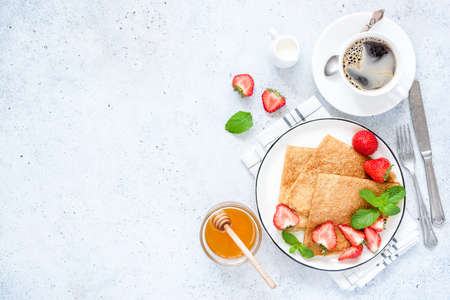 French Crepes or Russian Blini with fresh strawberries, honey, coffee on concrete background. Healthy Tasty Breakfast. Table top view, copy space 스톡 콘텐츠