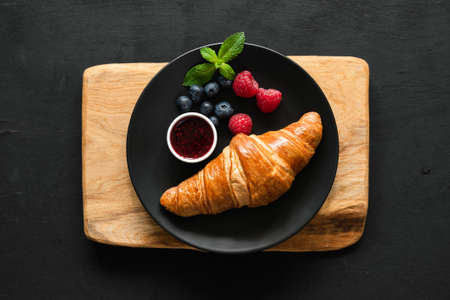 Croissant with berries and jam on black plate, table top view. 스톡 콘텐츠