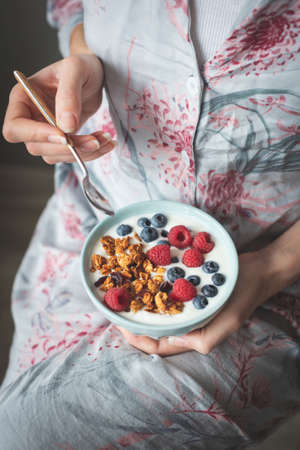 Unrecognizable female in pijama eating yogurt with granola, blueberries and raspberries. Concept of vegetarian breakfast, healthy eating, healthy lifestyle. Selective focus