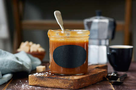 Salted caramel sauce in jar with empty tag for text, label or recipe. Selective focus Stock Photo