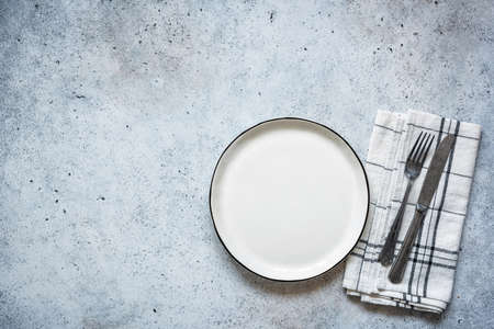 Table setting empty plate and cutlery on concrete background. Table top view. Top view Stock Photo