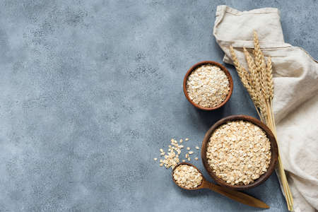 Rolled oats, oat flakes, whole grain oats in wooden bowl, linen textile and golden ears of wheat on concrete background with copy space for text