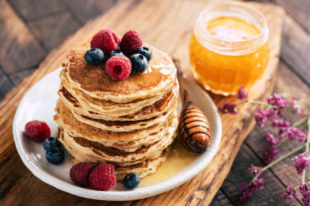 Oat pancakes with raspberries, blueberries and honey on wooden serving board